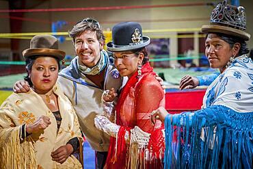 Lucha Libre. After the show. A follower is photographed with cholitas fighters. At left Julieta, in the middle Celia la Simpatica, and Dina , cholitas females wrestlers ,Sports center La Ceja, El Alto, La Paz, Bolivia