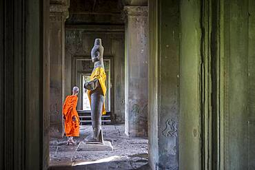 Monk and Buddha statue, in Angkor Wat, Siem Reap, Cambodia