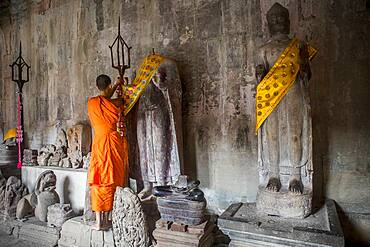 Monk embellishing religious sculptures, in Angkor Wat, Siem Reap, Cambodia