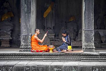 Monk blessing a woman, in Angkor Wat, Siem Reap, Cambodia