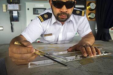 Officer calculating the course of the ship, ship's bridge, Ventus cruise ship, Nassau bay, near Cape Horn, Tierra de Fuego, Patagonia, Chile