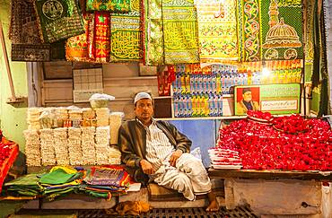 seller of religious offerings, souvenirs and wardrobe for shoes, entry to Hazrat Nizamuddin Dargah, Delhi, India