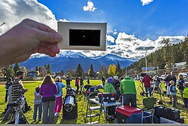 The partial solar eclipse of October 23, 2014 as seen from Jasper, Alberta, at a public event in Centennial Park as part of the annual Dark Sky Festival. This is a single-exposure image showing the scene near mid-eclipse with telescopes from volunteers from the Royal Astronomical Society of Canada, and the mostly clear skies above with the crescent Sun visible through the handheld polymer solar filter.