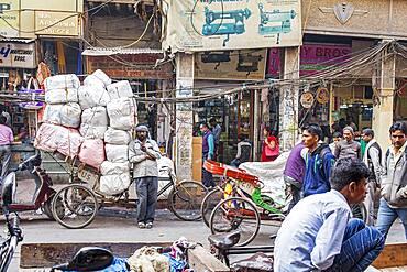 Carrier, resting and chatting through phone, in Nai Sarak street, near Chandni Chowk, Old Delhi, India