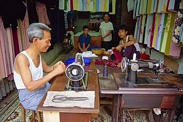 Tailor working at a sewing machine, and his family, in their shop in the old quarter of Hanoi, Vietnam, Indochina, Southeast Asia, Asia