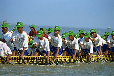 Men wearing baseball caps rowing a boat during the Water Festival in Phnom Penh, Cambodia, Indochina, Southeast Asia, Asia