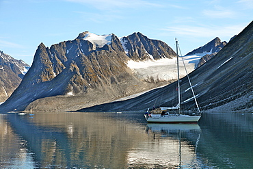 Yacht anchored under a glacier, Magdalenefjord, Svalbard, Norway, Scandinavia, Europe