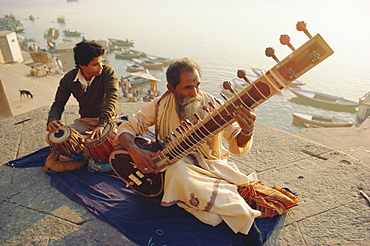 Musicians playing the Sitar and Tabla on the banks of the River Ganges (Ganga), Varanasi (Benares), Uttar Pradesh State, India