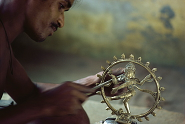 Man finishing off image of the dancing Siva, brass moulding workshop, India, Asia