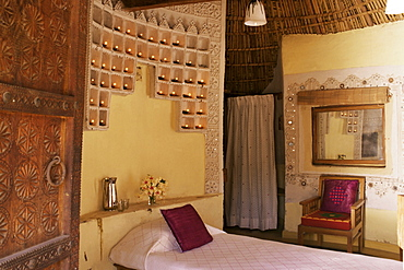 Raised mud reliefs inlaid with mirror on the walls in bedroom of modern home in traditional tribal Rabari round mud hut, Bunga style, near Ahmedabad, Gujarat state, India, Asia
