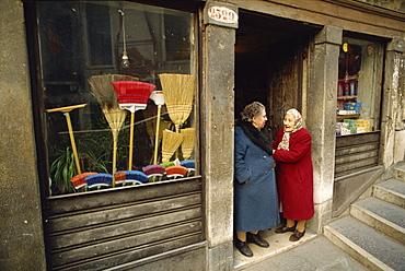 Two old ladies talking in the doorway of a broom shop in Venice, Veneto, Italy, Europe