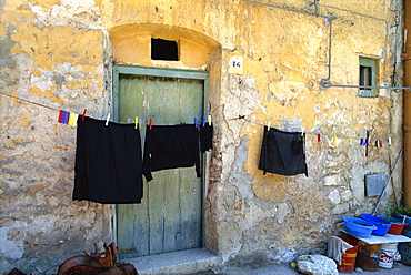 Clothes on a washing line outside an old house with peeling walls at Corleone on the island of Sicily, Italy, Europe