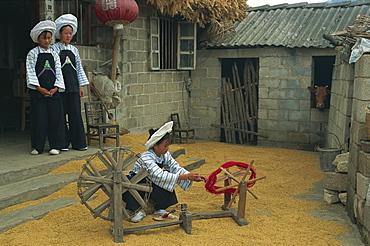 Bouyei girl winding a bobbin for weaving, south Guizhou, Guizhou, China, Asia