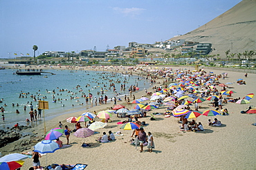 Tourists and holidaymakers crowd the beach at Playa La Lisera, in Arica, Chile, South America