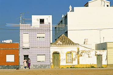 Women gossiping on the doorstep of a house on a street in small fishing village, Santa Luzia near Tavira in the Algarve, Portugal, Europe