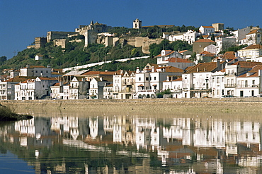 View of town and castle ramparts, reflected in Sado River, Alcacer do Sal, Portugal, Europe