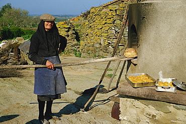Woman baking bread, Alentejo, Portugal, Europe