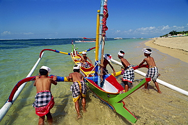 Men launching an outrigger fishing boat from Sanur Beach on the island of Bali, Indonesia, Southeast Asia, Asia