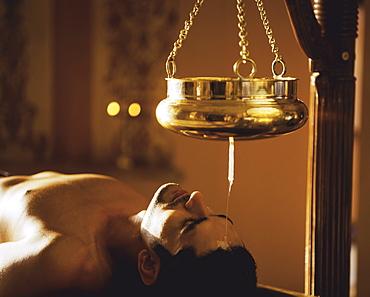 Young man taking Shirodhara treatment
