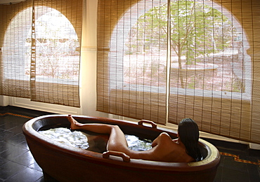 Girl inside the wooden bathtub at the Spa at Kalari Kovilakom, Kerala, India, Asia