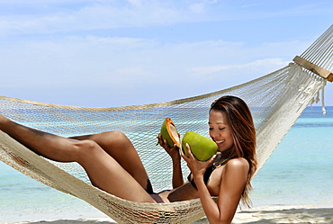 Girl on a hammock with fresh coconut, Bohol Beach, Philippines, Southeast Asia, Asia