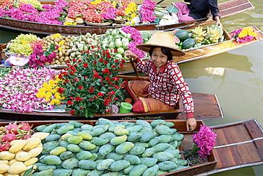 Market trader in boat selling flowers and fruit, Damnoen Saduak floating market, Bangkok, Thailand, Southeast Asia, Asia