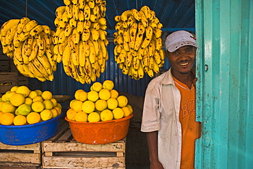 man standing next to Bananas in a market stall in Gonder, Gonder, Ethiopia, Africa