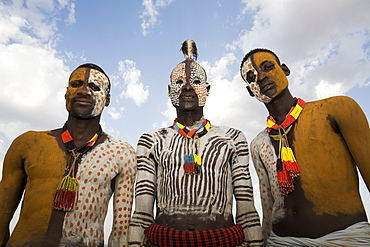Three Karo tribesmen with face and body decoration in chalk, imitating the spotted plumage of the guinea fowl, Omo river, Lower Omo Valley, Ethiopia, Africa