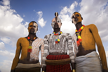 Portrait of three Karo tribesmen with faces and bodies painted with chalk imitating the spotted plumage of the guinea fowl, Omo river, Lower Omo Valley, Ethiopia, Africa