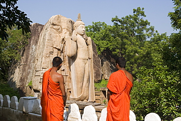 Buddhist monks in front of the giant standing statue of the Buddha dating from the 5th century, Aukana, Sri Lanka, Asia