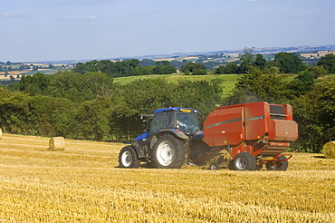 Tractor collecting hay bales at harvest time, seen from the Cotswolds Way footpath, The Coltswolds, Gloucestershire, England, United Kingdom, Europe