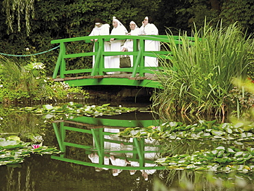 Four nuns standing on the Japanese bridge in the garden of the Impressionist painter Claude Monet, Giverny, Eure, Normandy, France, Europe