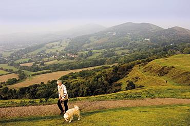Woman taking dog for a walk, British Camp, Hereford Beacon, Malvern Hills, Herefordshire, Midlands, England, United Kingdom, Europe