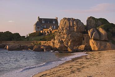 Beach house built behind rocks, Tregastel, Cote de Granit Rose, Cotes d'Armor, Brittany, France, Europe