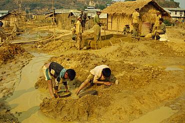 Children sieving and washing small gems from mine waste, Mogok ruby mines, near Mandalay, Myanmar (Burma), Asia