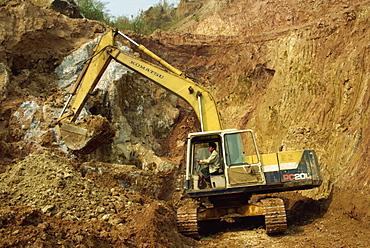 Machine digging gem-bearing clay in large open pit mine, Mogok ruby mines, Mandalay District, Myanmar (Burma), Asia