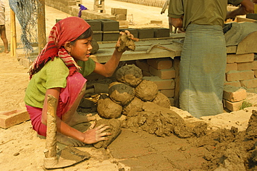 Child labour, young girl moulding lumps of clay at brickworks on Mandalay Plains, Myanmar (Burma), Asia