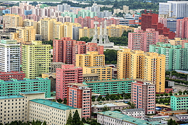 Workers' Party Monument amid painted blocks of flats, seen from Juche Tower, Pyongyang, North Korea, Asia