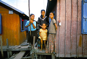 Girls standing by their house, floating fishing village of Chong Kneas, Tonle Sap lake, near Siem Reap, Cambodia, Indochina, Southeast Asia, Asia