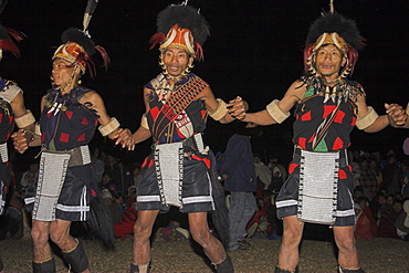 Naga men dancing at Grand Finale wearing headdress made of woven cane decorated with wild boar teeth, bear fur, topped with hornbill feather and tiger claw neckband also tiger teeth necklace, ivory armbands and apron decorated with cowrie shells, Naga New Year Festival, Lahe village, Sagaing Division, Myanmar (Burma), Asia