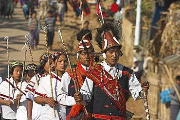 Naga New Year Festival, Naga people walking to festival ground, the men wearing headdress made of woven cane decorated with wildboar teeth, bear fur and topped with hornbill feather also with conch shell ear ornaments, Lahe village, Sagaing Division, Myanmar (Burma), Asia