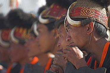 Naga tribes sitting on bench seating whilst the dignitaries make their speeches, they wear headdress made of woven cane decorated with wild boar teeth, and bear fur, Naga New Year Festival,  Lahe village, Sagaing Division, Myanmar (Burma), Asia