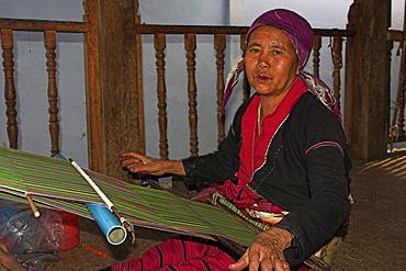 Wan Pauk village (Paulaung tribe) Paulang lady weaving on balcony of her house, Kengtung (Kyaing Tong), Shan State, Myanmar (Burma), Asia