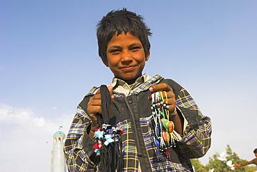 Street boy selling necklaces at the Shrine of Hazrat Ali, Mazar-I-Sharif, Balkh province, Afghanistan, Asia