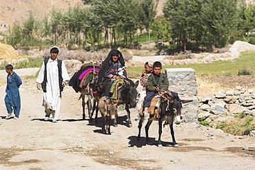 Aimaq people walking and riding donkeys entering village, Pal-Kotal-i-Guk, between Chakhcharan and Jam, Afghanistan, Asia