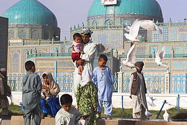 Family feeding the famous white pigeons, Shrine of Hazrat Ali, Mazar-I-Sharif, Afghanistan, Asia