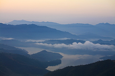 Clouds hover over lake at sunrise, Sikles trek, Pokhara, Nepal, Asia