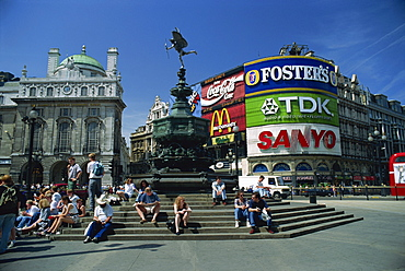 People sitting on steps below the Statue of Eros, Greek God of Love, erected in 1892 in memory of the Earl of Shaftesbury, Piccadilly Circus, London, England, United Kingdom, Europe