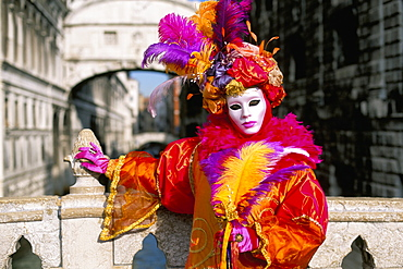 Portrait of a person dressed in mask and costume posing in front of the Bridge of Sighs, Venice Carnival, Venice, Veneto, Italy, Europe