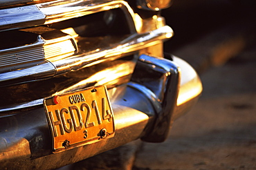 Close-up of chrome bumper and yellow car number plate in morning light, Havana, Cuba, West Indies, Central America